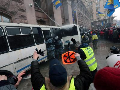 An dem von Regierungsgegnern besetzten Bürgermeisteramt in Kiew stiegen Uniformierte wieder in ihre Busse. Foto: Anatoly Maltsev