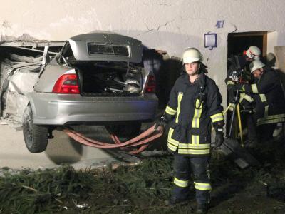 Rettunskräfte sind an der Unfallstelle in Ochsenhausen-Reinstetten im Einsatz. Nach einem 15-Meter-Flug war ein Auto in ein Wohnzimmer gekracht. Foto:Thomas Pöppel