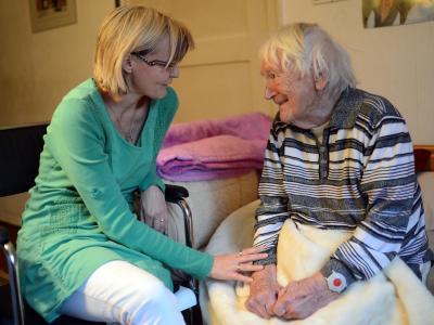 Eine Gutachterin vom Medizinischen Dienst der Krankenversicherung (MDK), spricht mit einer pflegebedürftigen Frau. Foto: Britta Pedersen