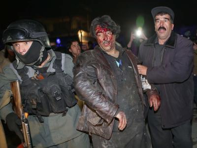 Afghanische Polizisten stützen ein Opfer desAnschlags in Kabul. Foto:S. Sabawoon