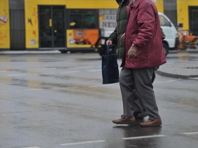 Blitzeis: Vorsichtig gehen eine Frau und ein Mann in Berlin über eine Kreuzung. Foto: Paul Zinken/dpa
