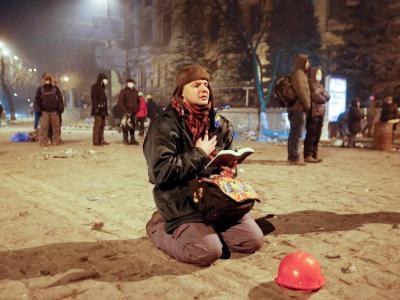 Hoffen auf Hilfe von oben. Ein Protestler betet mit der Biebel in der Hand. Foto: Sergey Dolzhenko