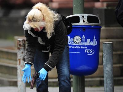 Eine Polizistin stellt vor dem Landgericht in Frankfurt am Main eine Pistole sicher. Foto: Daniel Reinhardt