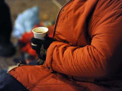 Ein Obdachloser wärmt sich in Berlin an einem Becher Tee. Foto: Maurizio Gambarini/Archiv