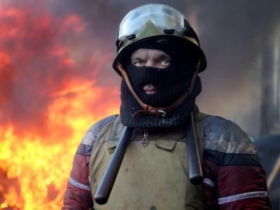 Ein maskierter Demonstrant vor einer brennenden Barrikade in Kiew.Foto: Zurab Kurtsikidze