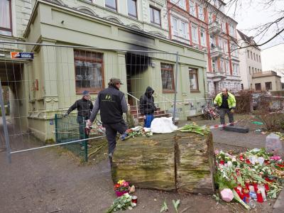 Arbeiter stehen in Hamburg vor dem ausgebrannten Mehrfamilienhaus. Foto: Georg Wendt