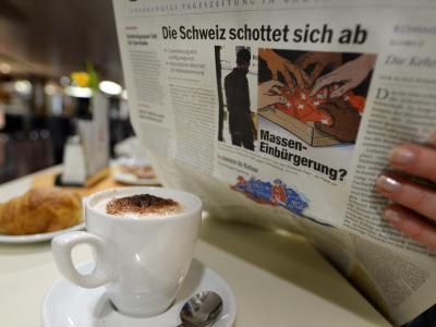 Eine Frau liest auf einer Fähre Richtung Konstanz eine Zeitung, die titelt