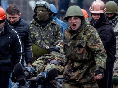 Polizisten bringen einen verletzten Kollegen inSicherheit. Foto: Yevgeny Maloletka