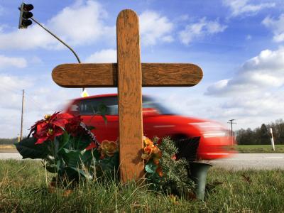 Ein Auto fährt an einem Holzkreuz vorbei, das an ein Verkehrsopfer erinnert. Foto: Jens Büttner