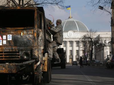 Ein Mann inspiziert einen zerstörten Lkw vor dem Parlamentsgebäudein Kiew. Foto: Maxim Shipenkov