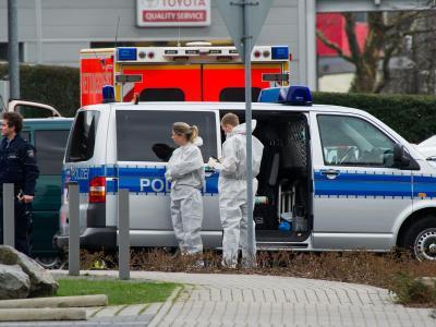 Einsatzfahrzeuge und Polizisten der Spurensicherung vor dem Bürogebäude, in dem eine Frau getötet wurde. Foto: Jan-Philipp Strobel