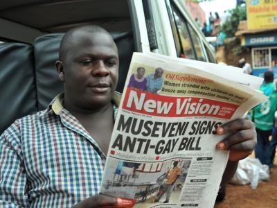 Ein Mann in der ugandischen Hauptstadt Kampala liest in einer Zeitung über das Anti-Homosexuellen-Gesetz. Foto: Ronald Kabuubi