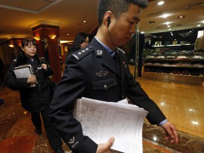 Ermittlungen: Ein chinesischer Regierungsbeamter mit Reisedokumenten. Foto: Rolex Dela Pena