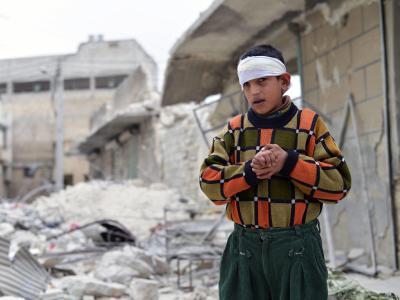 Das am 25.02.2014 veröffentlichte Foto zeigt einen verletzten Jungen, der nach einem Bombenangriff im syrischen Aleppo vor dem zerstörten Haus seiner Familie steht. Mindestens die Hälfte der vom Krieg vertriebenen Syrer sind nach UN-Angaben Kinder. Foto: