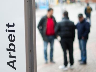 Männer stehen vor der Bundesagentur für Arbeit. Foto: Julian Stratenschulte/Illustration