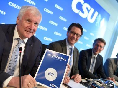 Der bayerische Ministerpräsident und CSU Vorsitzende Seehofer zeigt den gedruckten «Bayernplan», mit dem in der Sitzung zu beschließende CSU-eigenen Wahlkampfprogramm. Foto: Andreas Gebert