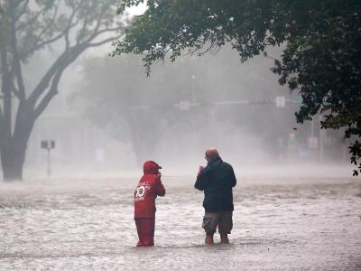 Reporter waten in Miami bei der Ankunft des Hurrikans «Irma» in Florida durch eine überflutete Straße. Foto:Wilfredo Lee