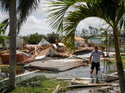 Ein Mann watet in Collier County vor seinem zerstörten Haus durch Hochwasser. Foto: Loren Elliott