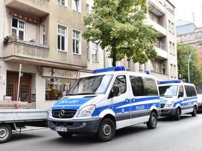 Polizeiwagen stehen während einer Razzia gegen Scheinehen vor einem Haus in Berlin. Foto: Paul Zinken