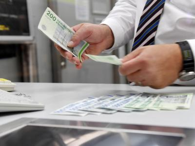 Ein Mitarbeiter zählt am Schalter einer Wechselbank dänische Kronen. Kommissionspräsident Juncker will den Euro in der gesamten EUeinführen. Foto:Tobias Hase