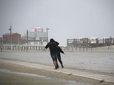 Spaziergänger stemmen sich am Strand von St. Peter-Ording gegen den ersten Herbststurm des Jahres. Foto:Wolfgang Runge