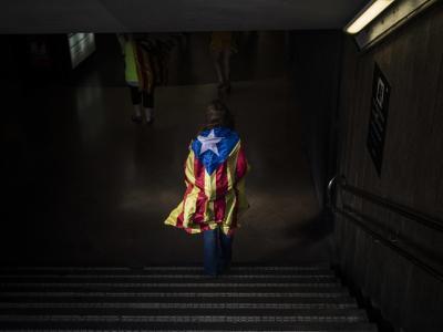 Eine in die katalonische Flagge, die «Estelada», gehüllt Frau in Barcelona. Foto: Santi Palacios
