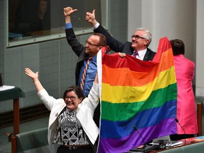 Die Parlamentsmitglieder Cathy McGowan, Adam Brandt und Andrew Wilkie präsentieren in Canberra eine Regenbogenfahne. Foto: Mick Tsikas
