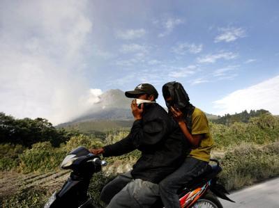 Zwei Indonesier fliehen auf einem Moped vor dem Vulkanausbruch. Der Mount Sinabung war am Sonntag zum ersten Mal seit 400 Jahren ausgebrochen.