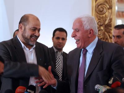 Der Hamas-Abgesandte Mussa Abu Marsuk (l) und Asam al-Ahmed von der Fatah besiegeln die Einigung mit einem Handschlag.