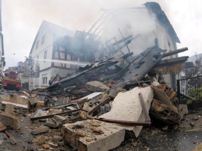 Feuerwehrleute und Rettungskräfte arbeiten an den Trümmern des explodierten Hauses in Weilrod-Riedelbach.
